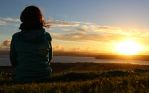 Auszeit_Frau schaut sich Sonnenuntergang an